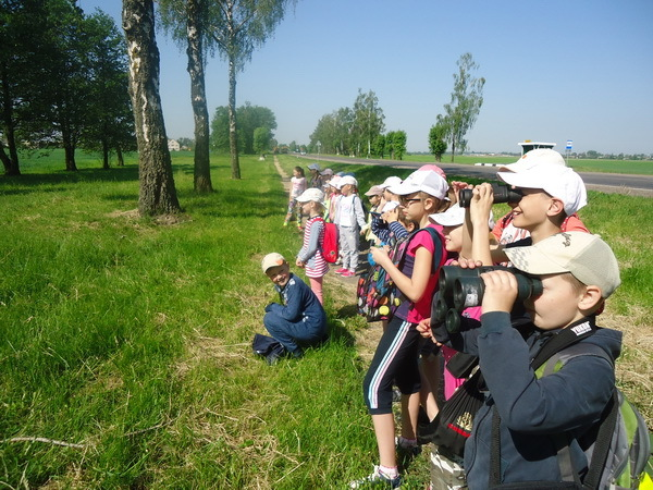 Belarus Students - Standing in Green Field - Looking Through Binoculars