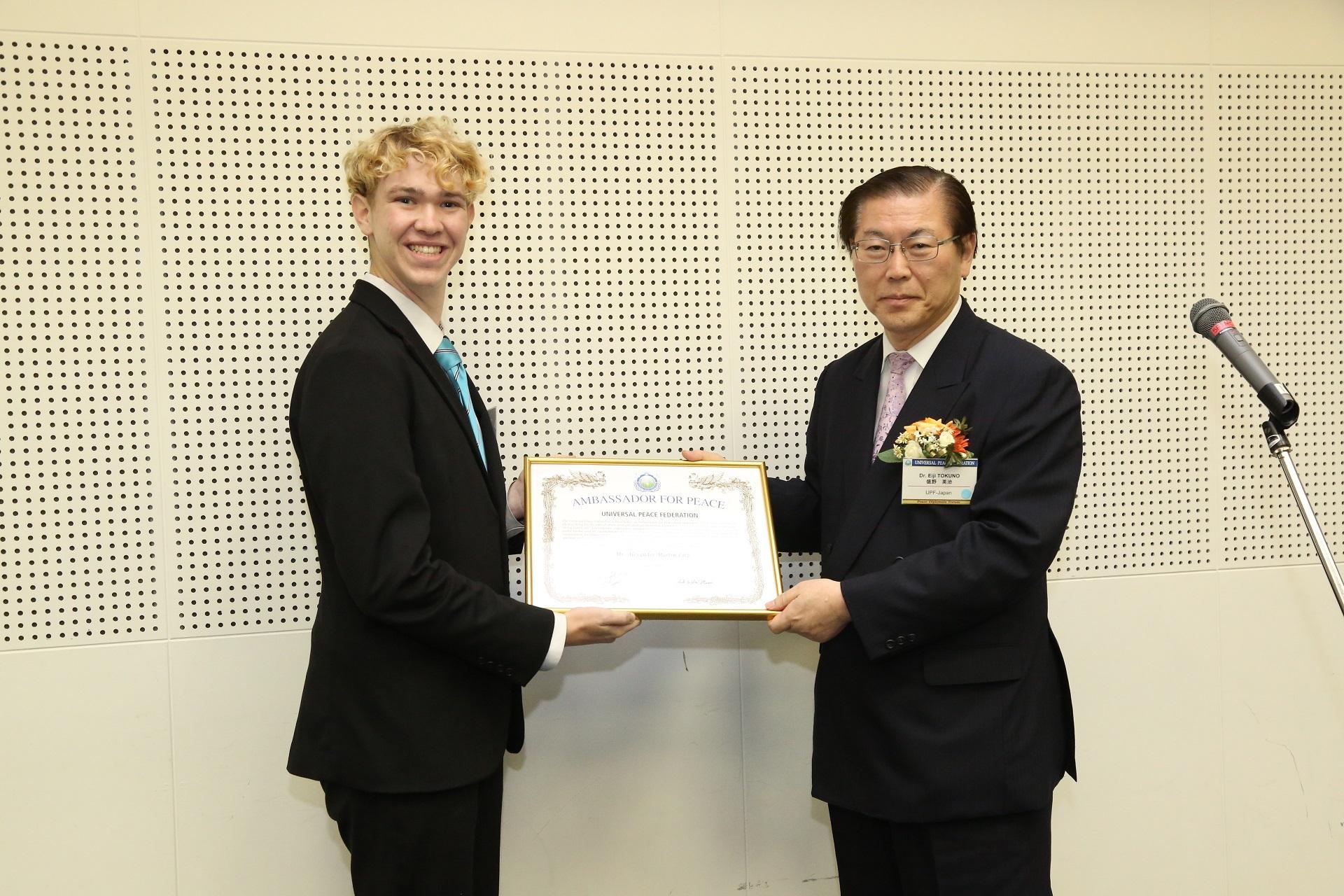 Alex receiving the Universal Peace Ambassador Award